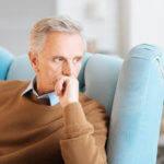 Pensive retired man recalling his memories