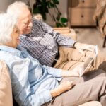 Senior couple looking at tablet on couch together